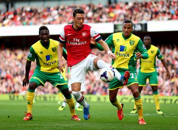 Hi-res-185347061-mesut-oezil-of-arsenal-is-watched-by-alexander-tettey_display_image