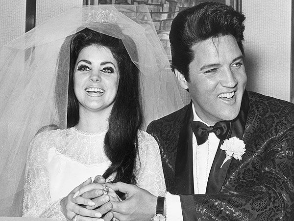 "Elvis opted for ""a black brocade silk tuxedo and Western boots,"" according to the Las Vegas Sun. Priscilla designed her own beaded chiffon gown, which was ""trimmed in seed pearls."" She stared at her new husband from beneath a three-foot veil that was ""secured by a rhinestone crown."""