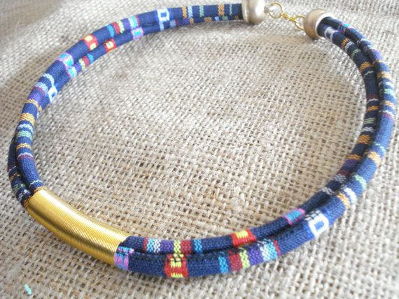 A bohemian blue colored necklace.  This wonderful necklace is a blue base rope necklace with a gold plated spring in the middle. Acrylic gold end cups