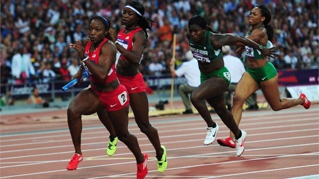 Bianca Knight of the United States receives the relay baton from Jeneba Tarmoh as Oludamola Osayomi of Nigeria takes the baton from teammate Gloria Asumnu in the women's 4 x 100m Relay Round 1 on Day 13 of the London 2012 Olympic Games at the Olympic Stadium.