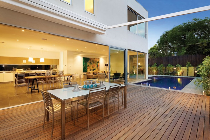 An alfresco entertaining area beneath a retractable roof sits next to a seductive, self-cleaning swimming pool in superb Jack Merlo landscaped gardens