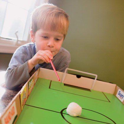 """Для воздушного футбола возьмите шарик для настольного тенниса, ватный шарик или помпон. На широком столе установите """"ворота"""" или просто определите, куда должен попасть шарик, чтобы был """"гол"""", или разметьте картонную коробку, как футбольное поле. Чтобы передвигать шарик, дуйте в трубочку или просто на шарик. Играйте вдвоем, вчетвером или большой компанией. Можно устроить и """"водный пинг-понг"""", гоняя шарик с помощью коктейльных трубочек в тазике с водой."""