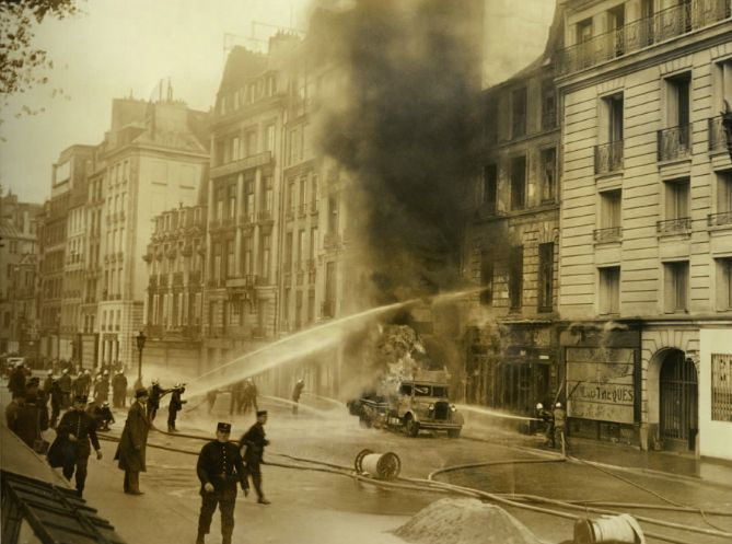 """""""Soldats du feu – Histoire illustrée des sapeurs-pompiers"""" d'Éric Deroo. Le 2 juin 1935, un camion-citerne qui livre de l'essence à la station-service s'enflamme. Six grosses lances et un camion générateur de mousse sont déployés. Pendant qu'un mur d'eau est dirigé vers les façades pour les isoler du camion en feu, d'autres jets refroidissent sa carcasse. Finalement, un cadavre carbonisé est retrouvé et sept personnes, dont une fillette, sont sauvées par les sapeurs."""