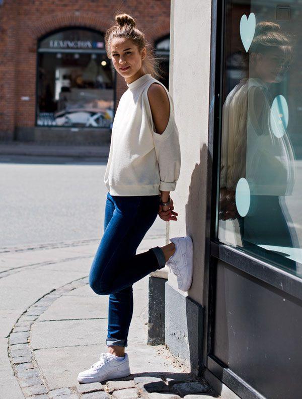 Look com calça jeans, blusa com cut out nos ombros e tênis da Nike branco.