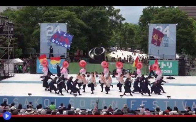 Ferrovieri giapponesi che ballano la Yosakoi Sopra un palco rapidamente costruito in mezzo ai giardini di Odori, nella ridente città di Sapporo, sono schierati in file successive trentadue individui in uniforme nera con accenti rossi, il berret #giappone #danza #feste #spettacolo