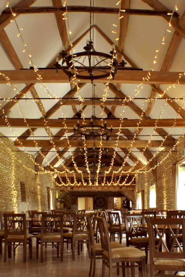 multi swag fairy light canopy running along wenmans barn for a stylish wedding - Multi Canopy Decor