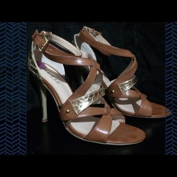 "Guess Tan and Gold Strappy High Heels Metallic Gold and Tan Strappy Guess Heels. Size 8 1/2. Straps around the ankle. All man made materials. The gold has a reptile pattern. Heels are approximately 4 1/2"" high. Guess Shoes Heels"