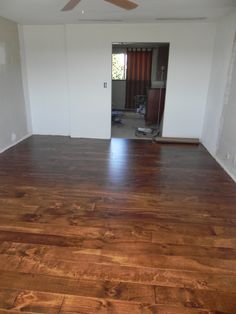 """Quarter inch plywood cut into 6"""" wide boards, sanded, secured to subfloor, stained and polyurethane coated."""