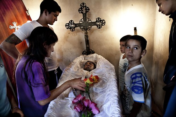 Funeral of Ezechiele's older brother, a victim of Paco (Lomas de Zamora, southern outskirts of Buenos Aires, Argentina; April 2012). The young man committed suicide throwing himself down from a bridge after smoking a big dose of Paco. It was Maria, the victim's mother, to summon the photographer to the funeral to take pictures of the body and the ceremony.
