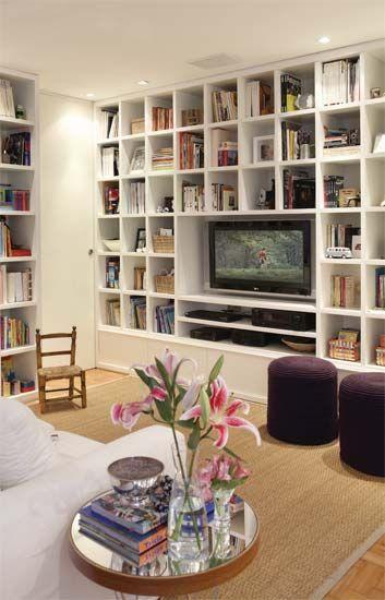Nichos exatamente iguais compõem o visual do móvel e emolduram o requadro maior, ocupado pela TV e por outros equipamentos. Laqueadas de branco-fosco, as estantes fazem com que a sala, de pouco mais de 10 m², pareça maior.