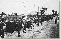 American prisoners carry their comrades  who are unable to walk during The Bataan Death March, 1942