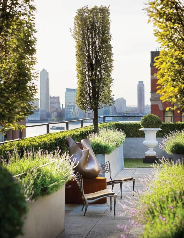 Narrowly pruned trees block unwanted views and demarcate the living space, which is appointed with  planters from Pennoyer Newman.