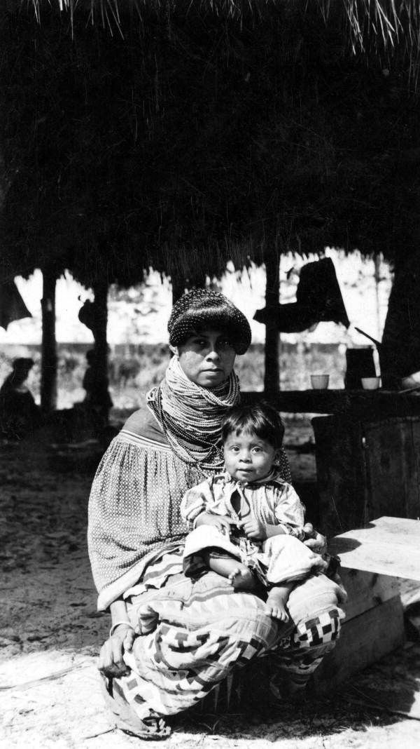 Displaced Seminole mother with her baby at a temporary camp in Immokalee, Florida. 1930