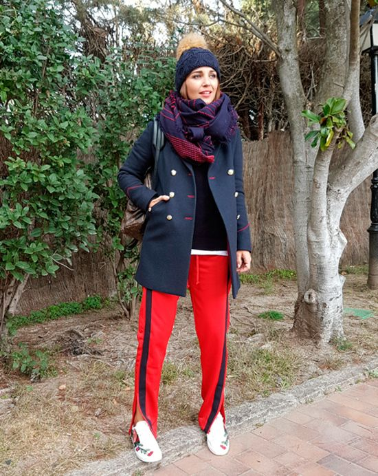 Tras la pista de Paula Echevarría » NAVY + RED. Navy knit sweater+red jogger pants with black ribbon+white floral embroidery sneakers+navy army style coat with red details+Louis Vuitton backpack+red and navy scarf+navy pompom knit beanie. Kinter Sport-Chic Outfit 2017