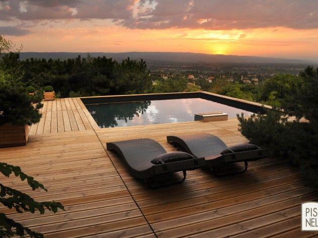 Piscine carrée avec terrasse en lame de bois. Deux transats ...