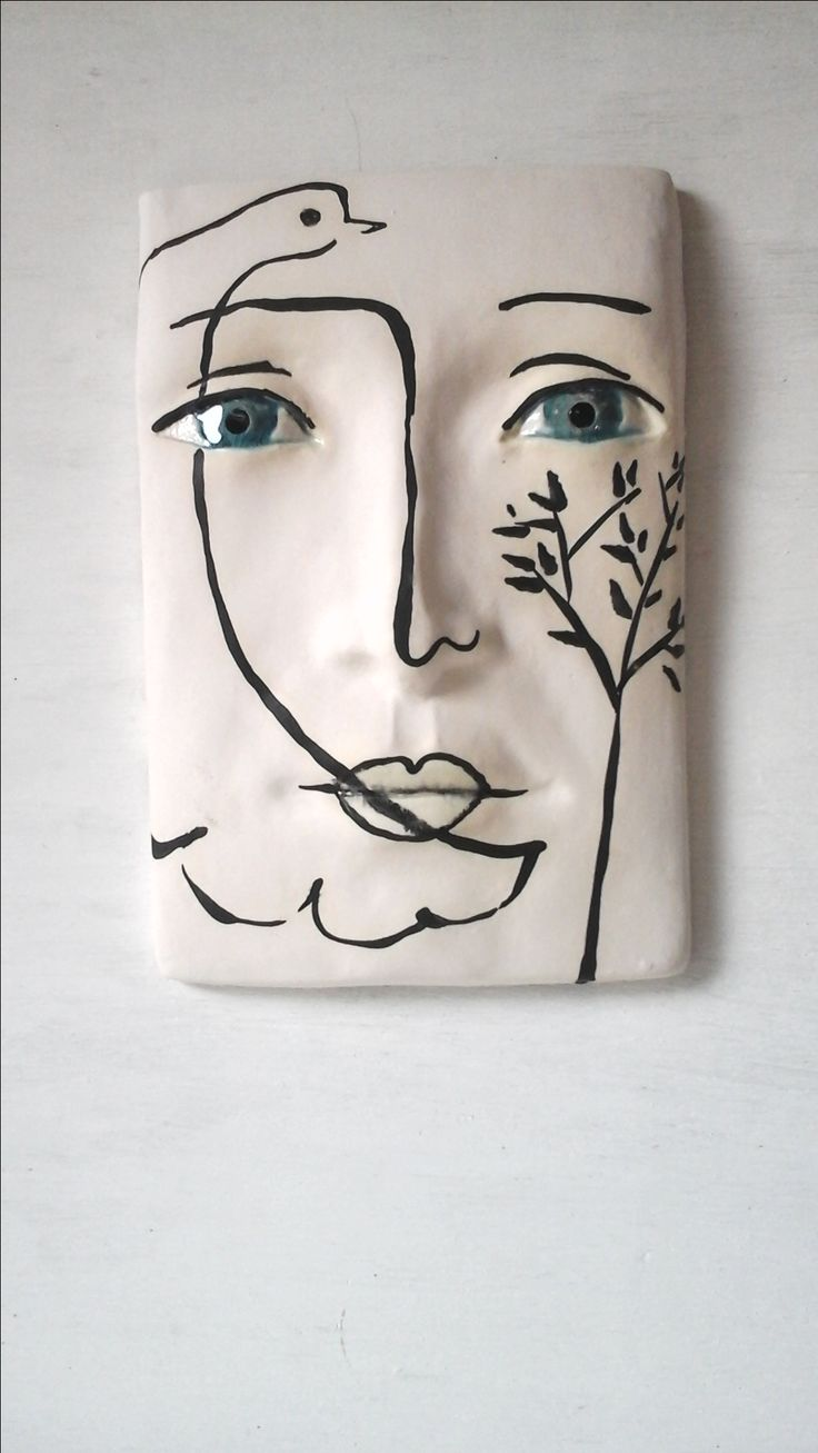 Ceramic wall sculpture of a low relief face over drawn with black slip dove and olive branch, a la Picasso.