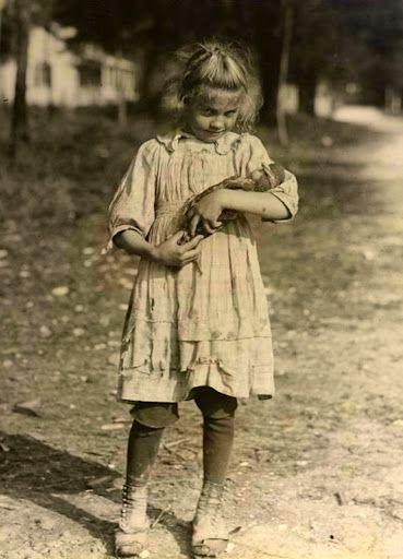 Cute little girl carefully cradling her doll, circa 1920's - 1930's.