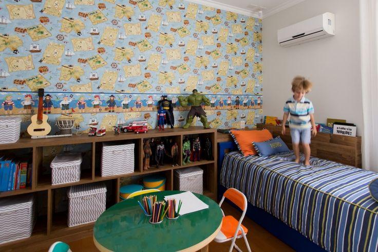 PEDRO ganhou um quarto espaçoso com papel de parede de pirata, estantel lotada de brinquedos e uma mesinha para desenhar. Projeto da CASA 128.