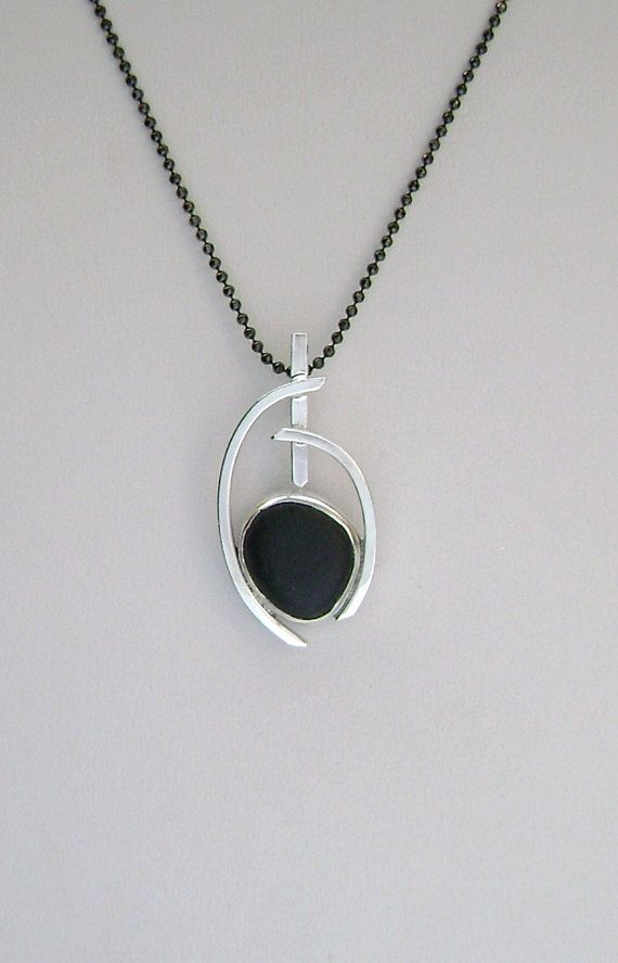 The rare black sea glass is genuine. It was found and supplied by....  https://www.etsy.com/shop/seawitchseaglass and is no back bezel set. The