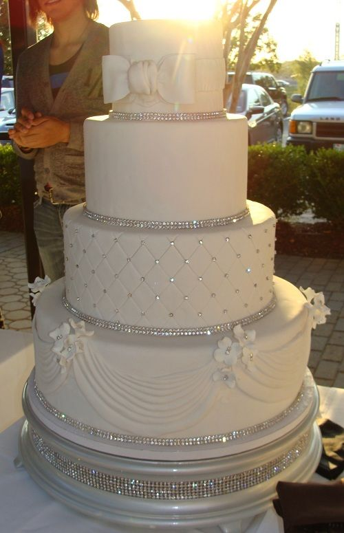 Love the rhinestones around the bottom of each tier!!!!! But I would add my wedding colors instead of a white bow make the bow a color and make the flowers the odors of my wedding also.