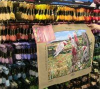 Tapestry of a Flock of Pink and White Cockatoos being held up against a rack of Tapestry Threads at Lee Nova Craft's St Marys Store