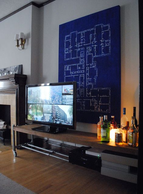 large architectural (or schematic) wall art, semi-industrial entertainment center, bar-style liquor lighting