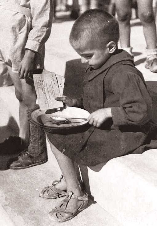 "Greece, 1941-1944. Μalnourished child holding ration coupon is about to try some soup from a soup kitchen; under German and Axis occupation Greeks were deprived from all food supplies produced in their country, which were sent to Axis troops waging war at the Eastern Front. Things got worse by Greek-run black market ""businessmen"". Consequently, death ratio due to famine raised to one of the highest in occupied Europe."