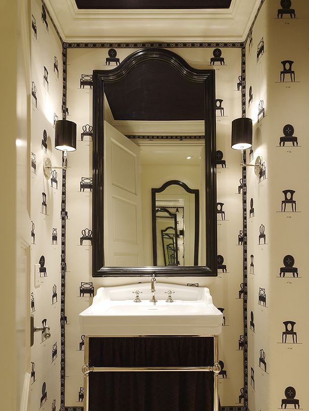 Great mirror and wallpaper in this little powder room.