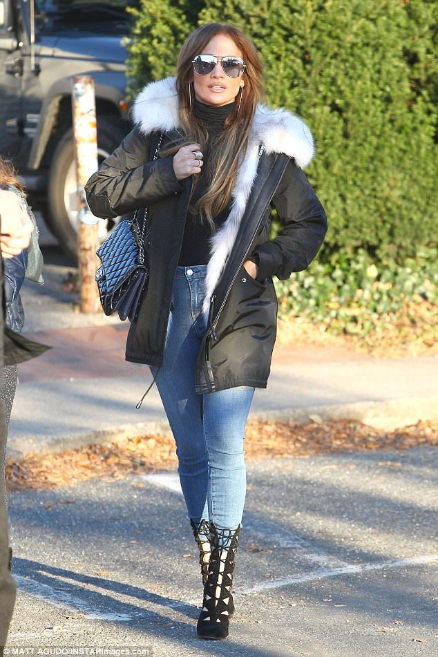 Chic in LI:Lopez wore a black turtleneck under a black parka jacket that had a white fur trim. The fur appeared to be real, not fake
