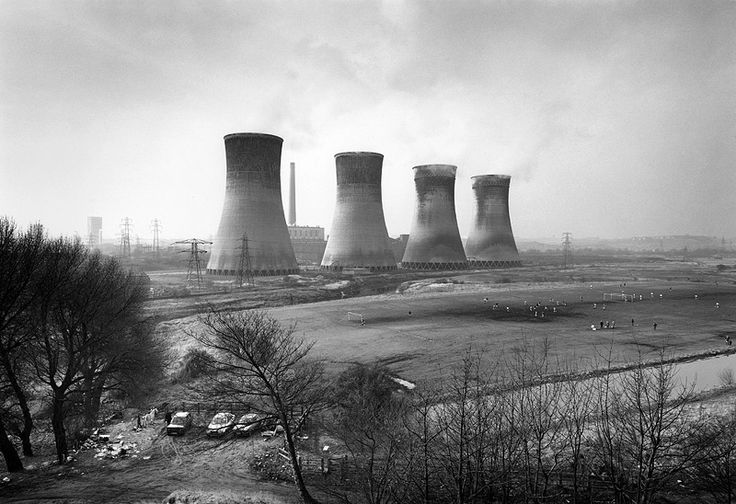 John Davies   A photography of people playing football but the power plant that's behind overtakes the image. This photo displays the scale of the people compared to the power plant. This photo is very bleak and has a theme of a change in life and value.