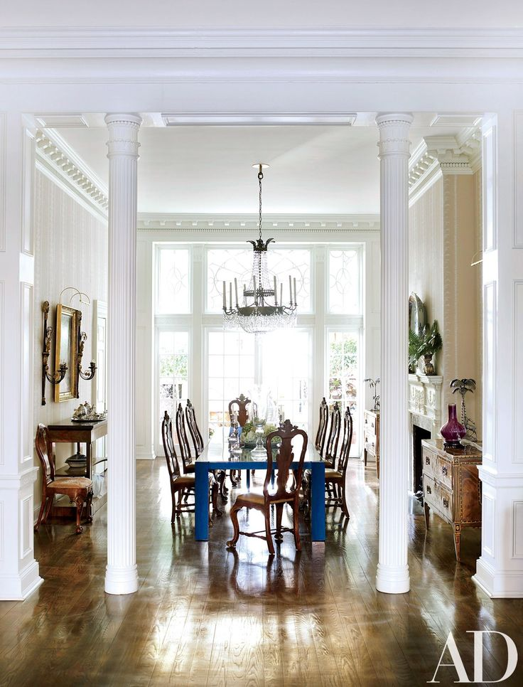 Fluted columns separate the drawing and dining rooms; the chandelier is Italian Empire.