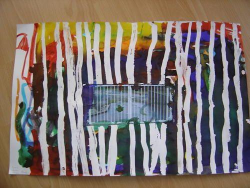 La photo du portail de l'école est placée au centre de la feuille avant le début de l'activité. Tracer des traits verticaux au drawing-gum. Passer de l'encre sur la feuille. Oter le drawing gum.