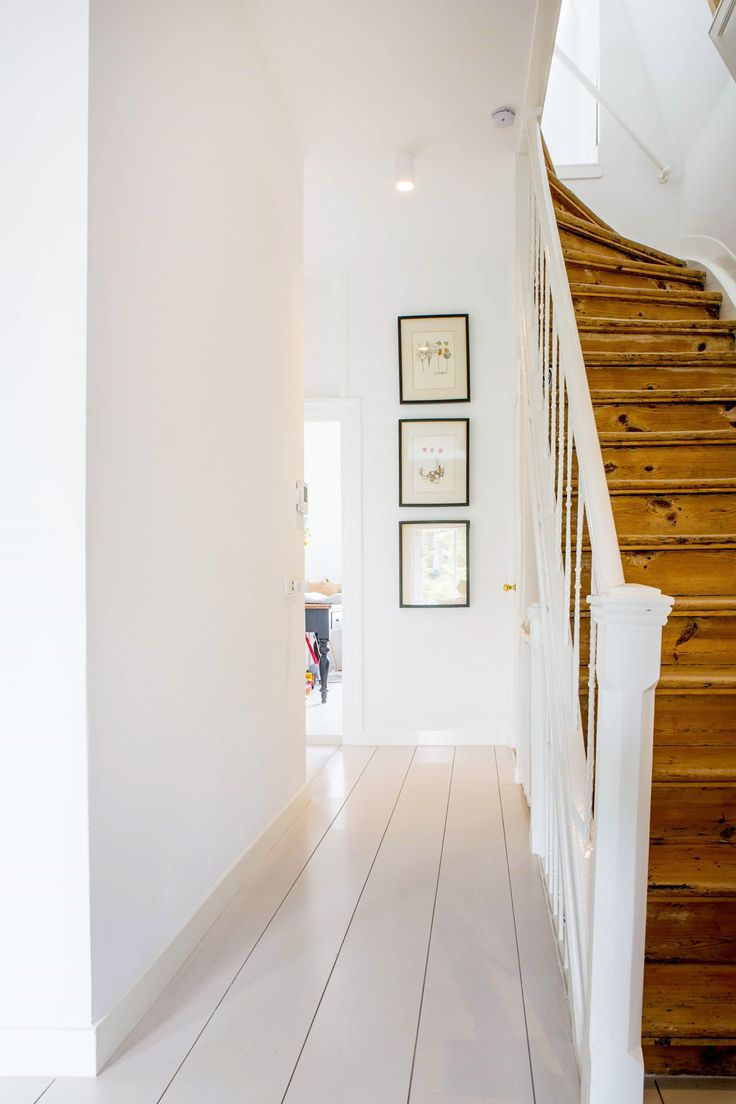 a fresh white hallway with hardwood stairs | curated and clean amsterdam house tour on coco kelley