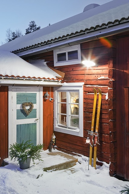 red wooden house in snow up close from Nordingarden blog