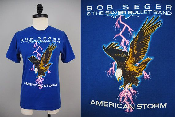 ❉ 1986 Vintage Bob Seger and the Silver Bullet Band American Storm Tour Tee ❉ Great graphic eagle with pink lighting running through it on the front of the shirt! ❉ Back lists tour dates for American Tour 1986 ❉ This design has been reprinted many times (even by Forever 21!) but this is the real original deal, with (c) 1986 below the front image and a Selec-T tag that dates this item to the 1980s ❉ Great for any Bob Seger fan! ❉ Condition: one knick in the sleeve and one small stain near…