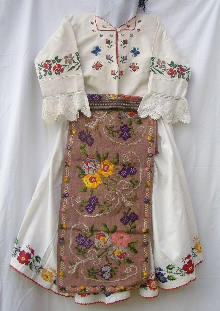 Costum femeiesc din cîmpia Banatului cu ie şi poale din pînză de in, cu motive florale, catrinţele ţesute din lînă și mătase colorată, cu motive florale