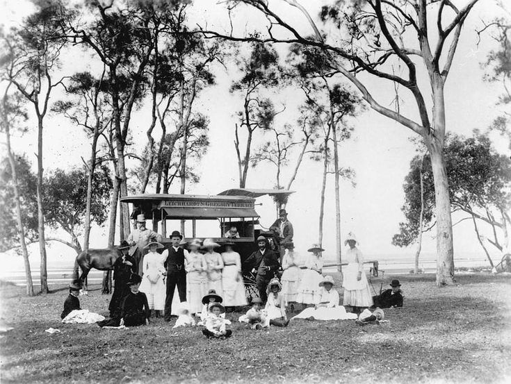Family group at a Lota picnic ground, Lota, Brisbane, 1880 -  The adults are standing in front of a horse drawn passenger carriage labelled Leichhardt's Gregory Terrace. The children are sitting on the grass in front of the adults.