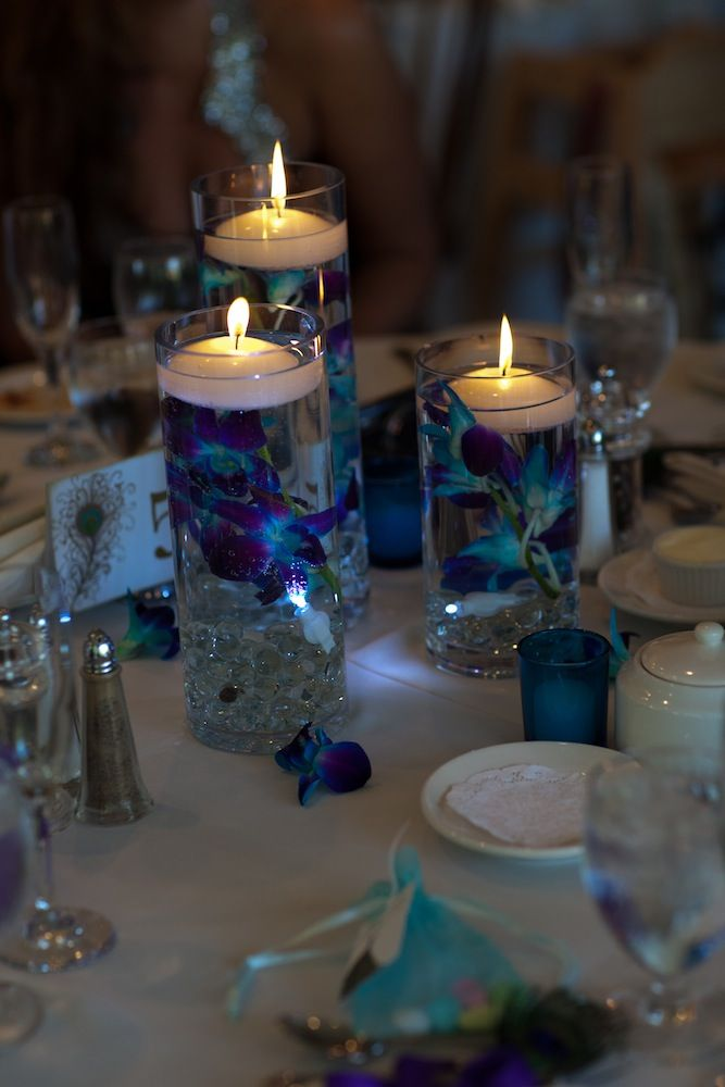 Sen banquet idea Any flowers could be used for this...and you can buy one size of the glass cylinders at the Dollar Tree.    Centerpieces: Blue dyed orchids submerged in water with floating candles on top. Marbles and LED light at the bottom of the cylinder vase. Loose orchids and blue votive candles on the table    Decorator: Elegant Affairs
