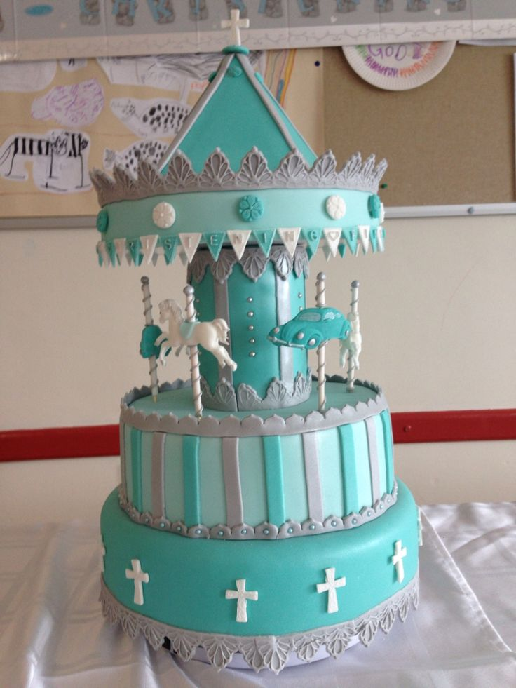 Carousel Cake waging rotates on a turntable. Was adapted to make a joint Christening Cake for a boy & a girl