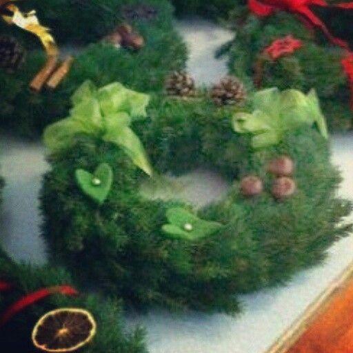 Granriskrans pyntad med kastanjer, kottar , filthjärtan, pärlnålar och gröna organzaband.