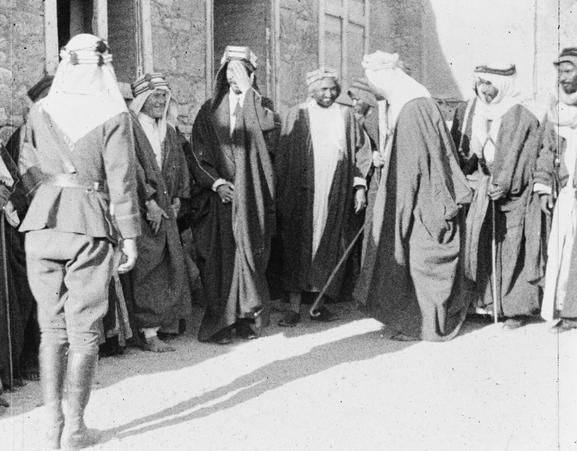 King Feisal greets Lovell Thomas. Colonel T. E. Lawrence is to the right of Feisal.
