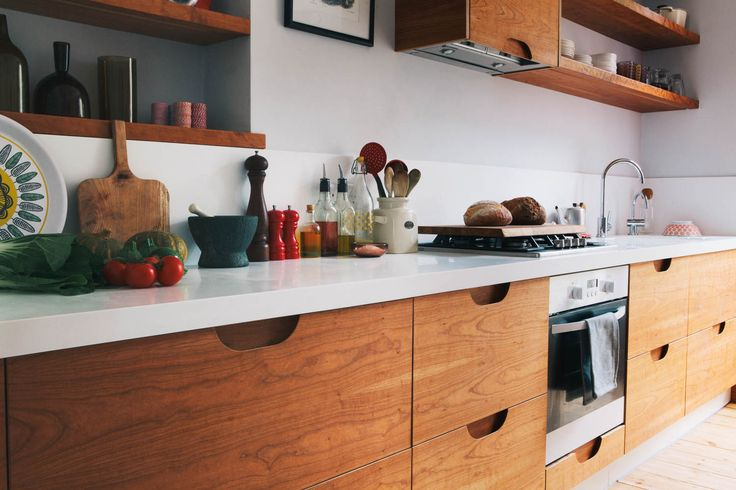 The scoop handles in this cherry veneered kitchen reveal the beautiful laminations of the birch plywood we've used to make the drawers fronts. The drawers are cut from the same piece of birch ply so the grain runs seamlessly from drawer to drawer.