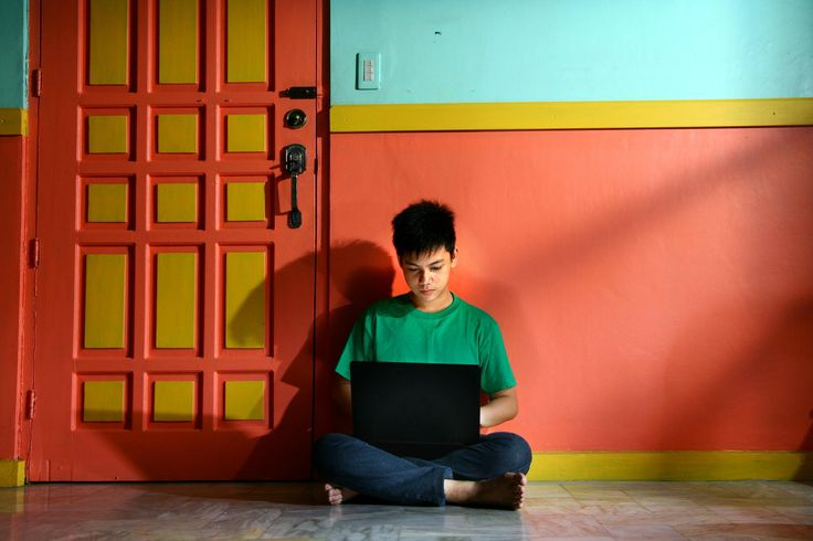 Young asian teen with a laptop in an empty living room of a house - Photo of a young asian teen with a laptop in an empty living room of a house