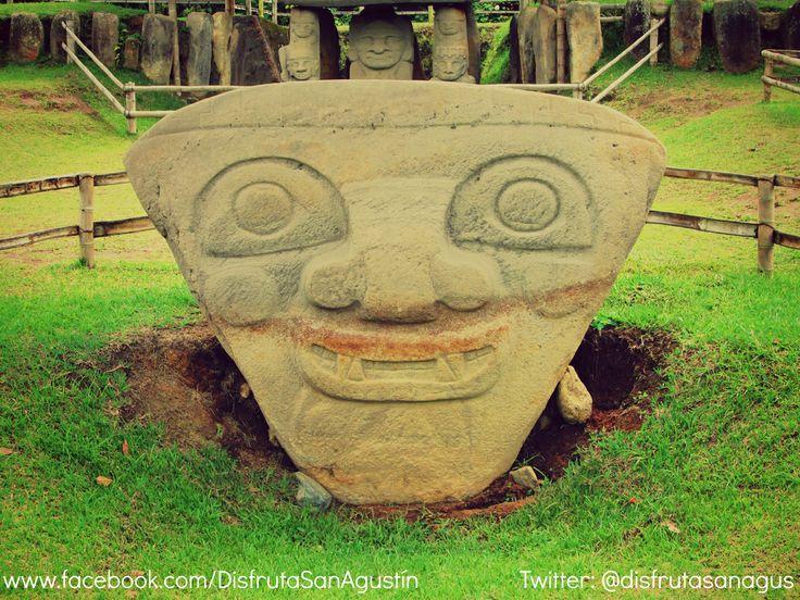 Este enorme rostro triangular de ojos abiertos que miran al oriente, de boca sonriente, colmillos cruzados y mejillas circulares, es llamada Deidad Solar. Mesita B, Parque Arqueológico de San Agustín