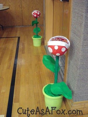 Dowel rods holding up a cut up plastic ball from WalMart that has been decorated to look like a piranha plant.
