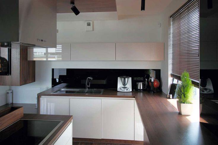 Kuchnia w zabudowie na wymiar dla bydgoskiego domu w odcieniach beżu i brązu o naturalnym odcieniu drewna.