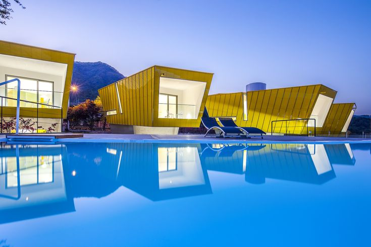MOAI in Chilean Easter Island by studio KOOSSINO. The 6000m2 site has a 10m slope. In order to make active use of the inclined plane, a horizontal mass was inserted in the core. The horizontal mass consisting of a gallery café and a pool at the upper part serves as a stylobate for the cutting area. An atypical mass of six buildings was put on the stylobate linked to the gentle slope