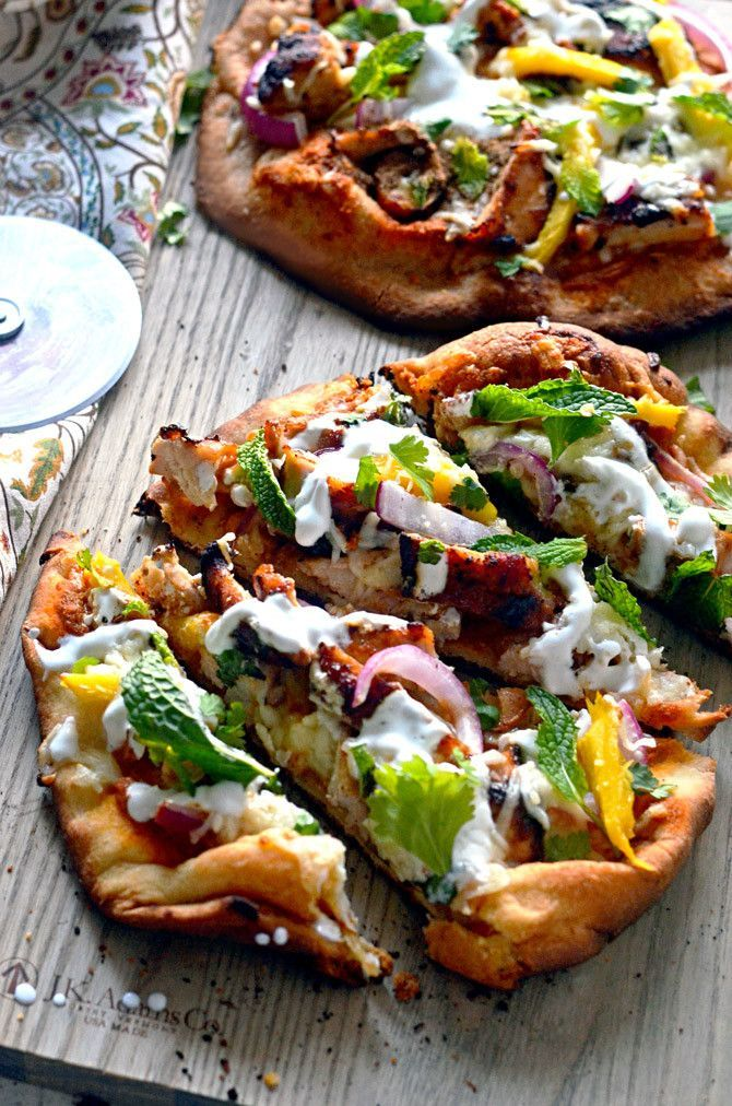 Tandoori Chicken Naan Pizzas. These grilled pizzas feature juicy tandoori chicken, mango, mozzarella, mint, cilantro, and yogurt. Premade naan make a great base for a delicious pizza dinner with Indian flair. | http://hostthetoast.com
