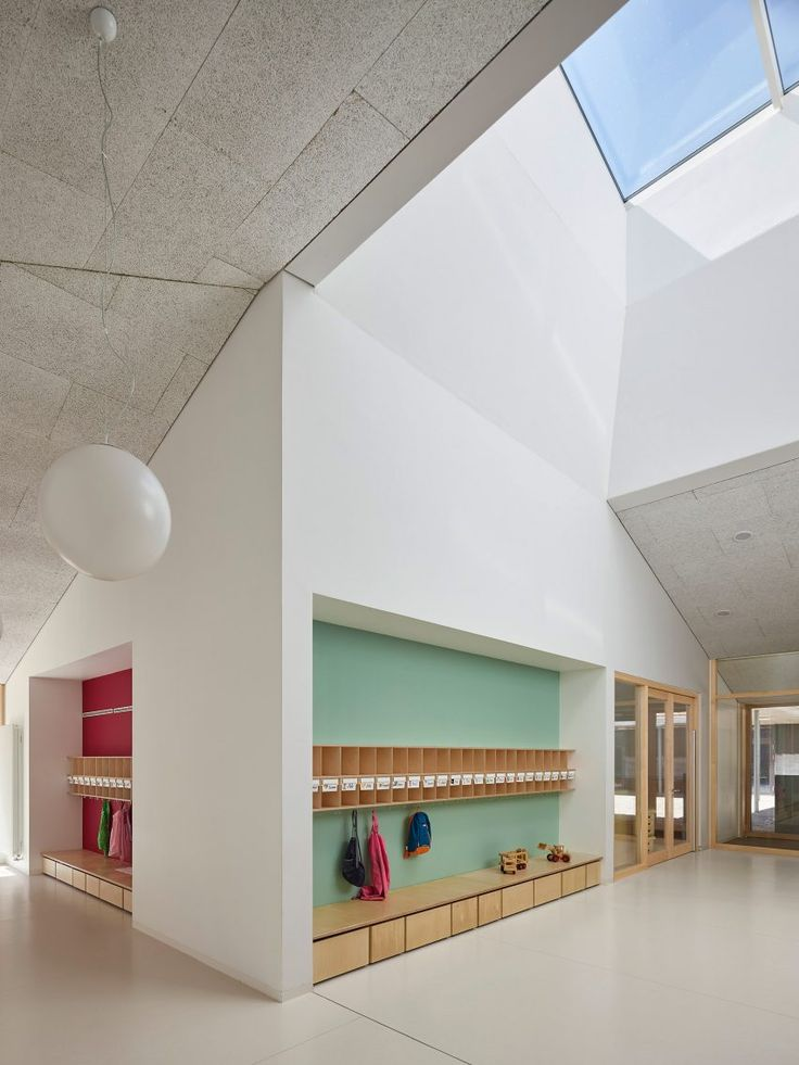 The entrance to this nursery leads to a multipurpose space containing coat hooks and storage, which is illuminated from above by the square skylight.
