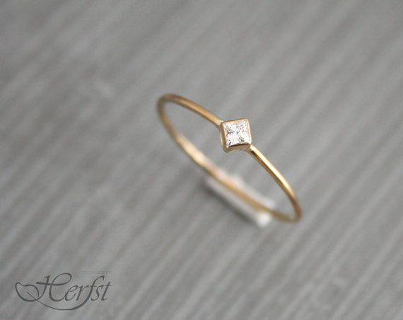 A real present for yourself or someone else! This lovely tiny 14k solid golden ring with a wonderfull Diamond. Its handmade of 1mm wire.  *Diamonds are a girls best friend*   Material: 14K solid yellow -, white-, or rosegold Diamond: .06 ct (2x2 mm), excellent princess cut, Top Wesselton, VVSI clarity, color F/G, conflict free.  Instead of Diamond you can also choose Moissanite. This gemstone is very similar to Diamond, only cheaper and also with a wonderfull sparkle!  Instead of 14K solid…